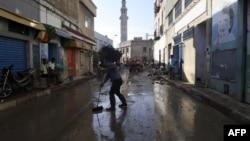 Des personnes en train de nettoyer la rue suite à une crue mortelle dans la ville de Dar Chaabane, en Tunisie, le 23 septembre 2018.