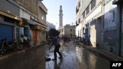 Des personnes en train de nettoyer les débris de la rue suite à une crue mortelle dans la ville de Dar Chaabane, en Tunisie, le 23 septembre 2018.