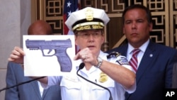 Columbus, Ohio, Police Chief Kim Jacobs holds up a photo showing the type of BB gun that police say a 13-year-old boy pulled from his waistband just before he was shot and killed by police investigating an armed robbery report, Sept. 15, 2016. Police say the boy, Tyre King, died at a hospital after the Wednesday evening shooting.