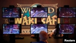 Visitors play ''World of Warcraft'' at an exhibition stand during the Gamescom 2012 fair in Cologne August 15, 2012. The Gamescom convention, Europe's largest video games trade fair, runs from August 16 to August 19. (REUTERS/Ina Fassbender)