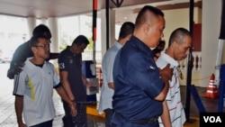 Keempat terdakwa, WNI yang divonis hukuman mati, dikawal oleh polisi di Pulau Penang, Malaysia, meninggalkan ruang sidang hari Senin, 7/10 (foto: Munarsih/VOA).