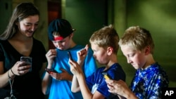 "In this Thursday, July 14, 2016, file photo, youngsters play during a ""Pokemon Go"" event at Memorial Stadium in Lincoln, Neb. (AP Photo/Nati Harnik, File)"
