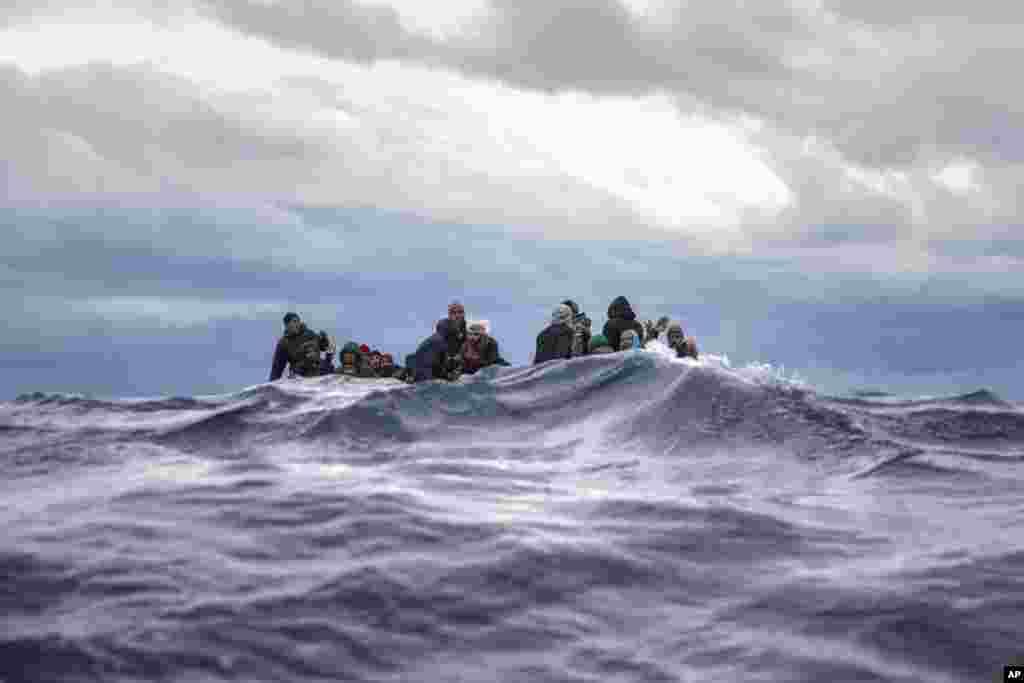 پناهجویان از مراکش و بنگلاش که با قایق خود روی دریای مدیترانه سرگردان بودند منتظر کمک امدادگران اسپانیایی هستند.