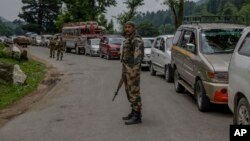 An Indian border security force soldier stands guard at a temporary checkpoint near a pilgrim base camp near Pahalgam, about 100 Kilometers south of Srinagar, Indian controlled Kashmir, July 11, 2017.