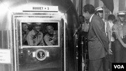 El presidente Richard M. Nixon habla con los astronautas del Apolo 11, Neil Armstrong, Michael Collins y Edwin Aldrin. Los astronautas se encuentran dentro de la estación móvil en cuarentena tempora después de su regreso a la Luna.