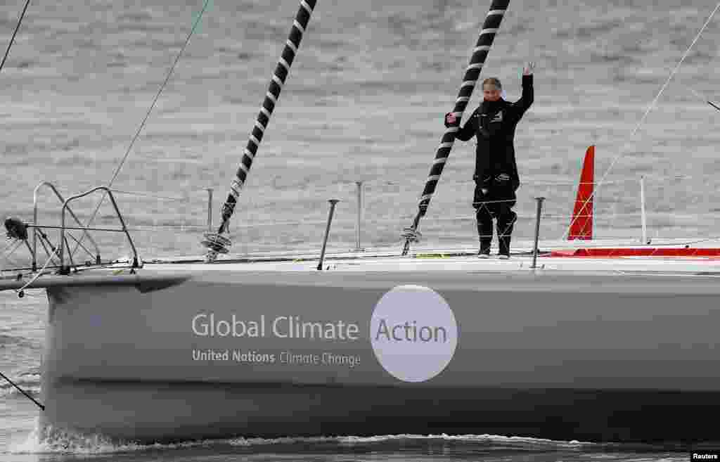 Swedish teenage climate activist Greta Thunberg waves from a yacht as she starts her trans-Atlantic boat trip to New York, in Plymouth, Britain.