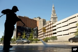 FILE - A worker cleans the sidewalk in front of Quicken Loans Arena in Cleveland, Aug. 5, 2015, before a Republican presidential candidates debate. The arena will also be the site of the party's national convention July 18-21.