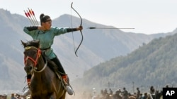 In this photo taken on September 6, 2018, a women shoots an arrow in a competition during the Third Nomad Games, in Cholpon-Ata, 250 kilometers from Bishkek, Kyrgyzstan. (AP Photo)