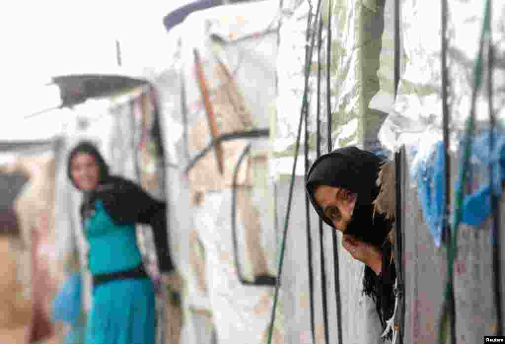 A Syrian refugee looks out of her tent in a camp in Tyre, southern Lebanon January 31, 2013.