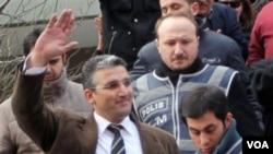 Nedim Sener, wartawan harian Milliyet, melambai kepada massa saat polisi Turki menahannya di Istanbul (foto: dok). Beberapa wartawan Turki dituduh terlibat dalam rencana kudeta.