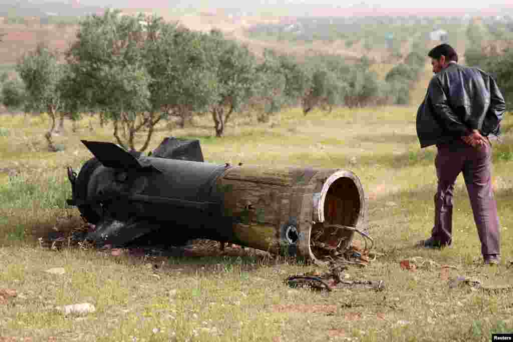 A man inspects a piece of a rocket that landed south of Daraa Al-Balad, Syria.