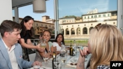 Antoinette Mazzaglia, of Taste Florence, shows tourists how to read a wine label at the Golden View Open Bar overlooking Florence's Ponte Vecchio.