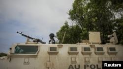 Một cảnh sát người Uganda phục vụ với Phái bộ của Liên hiệp Phi châu trong đơn vị cảnh sát được thành lập đầu tiên của Somalia, đứng trên chiếc xe thiết giáp tại một trạm cảnh sát trong thủ đô Mogadishu