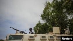 参加非盟组织的索马里警察部队的乌干达警官与摩加迪沙一警察局外站在载人装甲车上