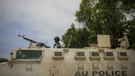 Ugandan police officer serving with the African Union Mission in Somalia's first Formed Police Unit stands at the top of an armored personnel carrier at a police station in the capital Mogadishu, August 7, 2012.