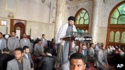 In this Friday, May 13, 2011, file photo, radical Shiite cleric Muqtada al-Sadr is surrounded by bodyguards as he speaks at Friday prayers in Kufa, 160 kilometers (100 miles) south of Baghdad, Iraq.