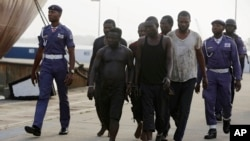 FILE - In this Feb. 22, 2016, photo, Nigeria naval officers escort arrested pirates that hijacked the Panama-flagged Maximus vessel.