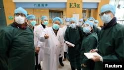 Pakar dari China dan Organisasi Kesehatan Dunia (WHO) mengenakan masker saat mengunjungi Rumah Sakit Wuhan Tongji, pusat wabah virus corona di Hubei, China, 23 Februari 2020. (Foto: China Daily via Reuters)