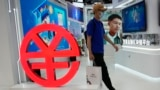 A visitor passes by a logo for the e-CNY, a digital version of the Chinese Yuan, displayed during a trade fair in Beijing, China, Sunday, Sept. 5, 2021. (AP Photo/Ng Han Guan)