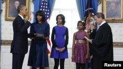 Presiden AS Barack Obama (kiri) saat diambil sumpahnya oleh Ketua Mahkamah Agung AS John Roberts disaksikan oleh ibu negara Michelle Obama dan kedua puterinya, Malia dan Sasha di Gedung Putih hari Minggu (20/1).