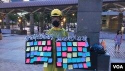 """一位自稱參加了香港""""反送中運動""""所有大遊行的香港女學生在台北車站廣場舉起""""連儂板""""。(2019年7月27日,美國之音林楓拍攝)"""