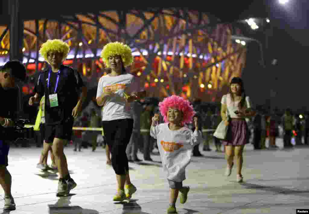 """A family runs around the """"Bird's Nest"""", also known as the National Olympic Stadium, during a night running party to mark the six-year anniversary since the Beijing Olympic Games, in Beijing."""