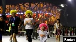"""Una familia china camina por el """"Nido de aves"""", como se conoce al estadio Olímpico de Beijing. La ciudad fue escogida como sede de las Olimpiadas de Invierno de 2022."""
