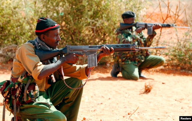 FILE - Kenyan policemen hold their position while patrolling the Kenya-Somalia border near the town of Mandera, Feb. 6, 2015.