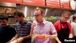 Steve Ells, centre, PDG de Chipotle Mexican Grill, mange un burrito dans un restaurant de New York Chipotle, 6 juin 2008