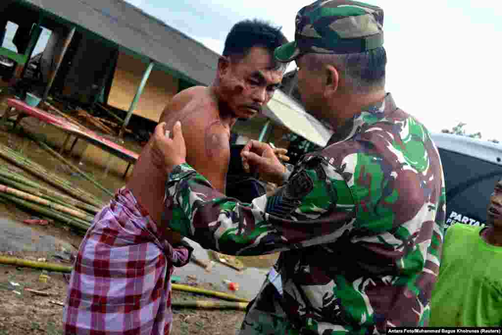 A soldier examines a local resident who was injured following a tsunami that hit at Tanjung Lesung district in Pandeglang, Banten province, Indonesia, Dec. 23, 2018.