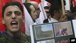 """這名親政府的敘利亞抗議者星期四在大馬士革舉著標語牌﹐上面寫著﹕""""我們看到你們在伊拉克和利比亞的自由。"""""""