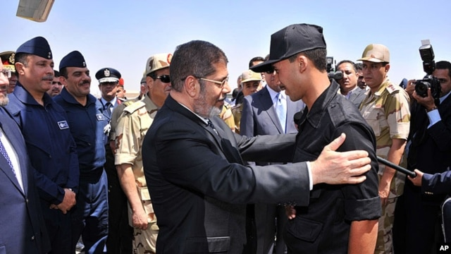An image released by the Egyptian Presidency shows Mohammed Morsi (C) embracing an Egyptian policeman after he was freed from captivity, in Cairo, May 22, 2013.