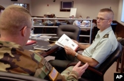 "Major Jeff Jennings, right, talks with Captain Joseph Scanlin before the start of a talk by writer McKay Jenkins during a workshop sponsored by the National Endowment for the Arts at the 10th Mountain Division in Fort Drum, N.Y., June 5, 2004. While in Afghanistan, Jennings sent home descriptive emails to his wife called ""News from the Edge of the Empire."" The emails became so widely circulated that West Point cadets were given some of them as assigned reading. Dubbed ""Operation Homecoming"" by the NEA, about 45 soldiers sat through the first session."