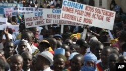 People originally from northern Mali carry signs reading 'We support army action to liberate the North,' as thousands of Malians, including elected officials, front, marched in support of foreign aid and military intervention to retake Mali's north from I
