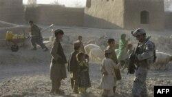 1 binh sĩ Mỹ bắt tay 1 cậu bé Afghanistan trong khi đang tuần tra ở huyện Panjwai, Afghanistan, 22/11/2010
