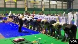 Anggota Syiah dari Sampang, Madura, Jawa Timur, shalat berjamaah di tempat pengungsian dalam gedung olahraga. (VOA/Petrus Riski)