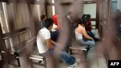 Part of a group of fourteen suspected members of a ring of human traffickers are kept in a holding cell in court in Guatemala City, August 9, 2012.