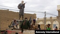 Fighters from Islamist group Ansar Dine stand guard as they prepare to publicly lash a member of the Islamic Police found guilty of adultery, in Timbuktu, Mali. (Aug 31, 2012 file photo)