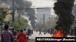Myanmar, Mandalay, Tires burn on a street as protests against the military coup continue