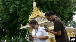 Thai reporters play Pokemon Go on their phone in front of a spirit house at a Government building in Bangkok, Thailand, Aug. 8, 2016.