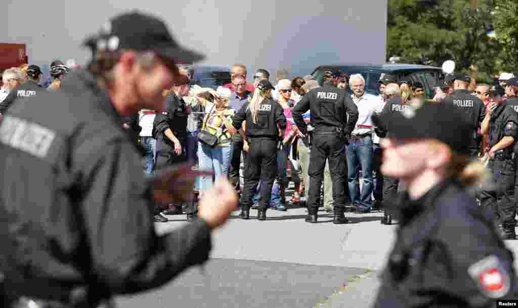 People gather nearan asylum center during a visit of German Chancellor Angela Merkel, in the eastern German town of Heidenau, near Dresden, Aug. 26, 2015.