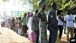 People wait to vote outside a polling station in Serrekunda, southwest the capital Banjul, during the presidential elections. Gambians voted in polls, which some observers said were skewed in favor of incumbent Yahya Jammeh, who heaped scorn on criticism
