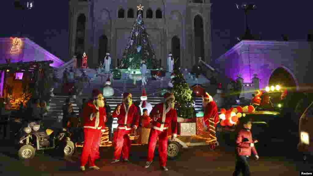 Des hommes déguisés en Père Noël célèbrent Noël dans le village de Jiyeh au Sud de Beyrouth, 23 décembre 2014.