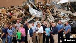U.S. President Barack Obama (at lectern) delivers remarks on the grounds of tornado-damaged Plaza Towers Elementary School in Moore, Oklahoma, May 26, 2013. Obama arrived in Moore on Sunday to tour the town that was hammered last week by a powerful tornad