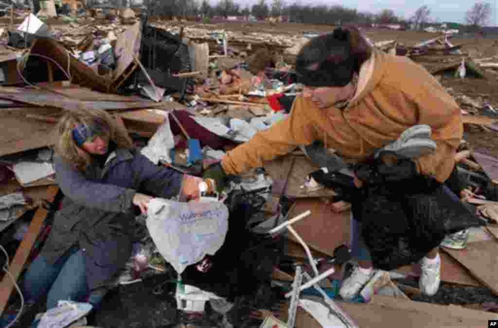 Unidentified women search through debris of Ted and Brenda Tolbert's Holton, Ind. home Sunday, March 4, 2012.