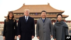 President Donald Trump, first lady Melania Trump, left, Chinese President Xi Jinping, second right, and his wife Peng Liyuan, right, stand together as they tour the Forbidden City, Nov. 8, 2017, in Beijing.