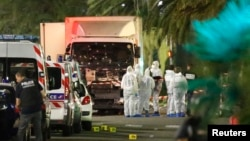 French police force and forensic officers early Friday look at the truck that ran into a crowd celebrating the Bastille Day in Nice, France, July 14, 2016.