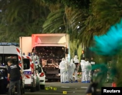 French police force and forensic officers early Friday look at the truck that ran into a crowd celebrating the Bastille Day national holiday in Nice, France, July 14, 2016.
