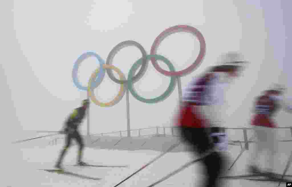 Cross-country skiers train in front of the olympic rings at the Laura biathlon and cross-country ski center, at the 2014 Winter Olympics, Feb. 17, 2014.