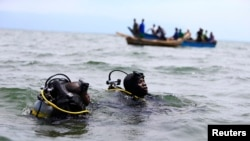FILE -Members of the Uganda Police Marine Unit participate in rescue efforts after a boat carrying mostly Congolese refugees capsized in Lake Albert southwest of Uganda's capital, Kampala, March 23, 2014.